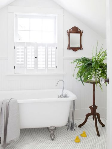 In this century-old Oregon farmhouse, an ornate Eastlake plant stand pops against the bathroom's spare Rejuvenation tub and white subway tiles. The flattering flooring would look great paired with a new Omega vanity. #OmegaVanityMakeover via @Country Living Magazine