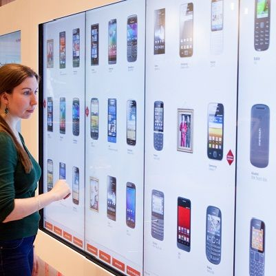 "This giant point of sale interactive touch screen is made up of 4 55"" portrait screens and allows customers to browse through mobile phone handsets. The Acquire team specifically developed a web-based CMS system for the mobile wall, enabling staff to make instant changes and updates to on screen content."