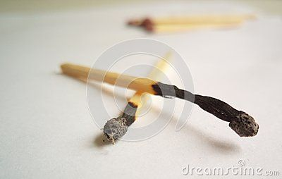 Closeup of burnt matchsticks on a white background.