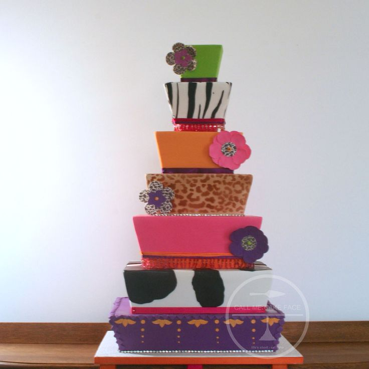 A bold cake in layers of animal print, flurescent colours and printed sugar flowers.  Off set tiers create a whimsical fun cake.