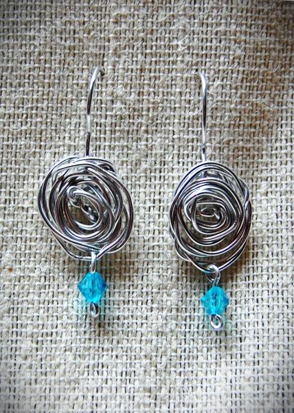 Pendientes de alambre de aluminio plateados con forma de rosas y decorados con abalorios azules. Se pueden realizar en otros colores.