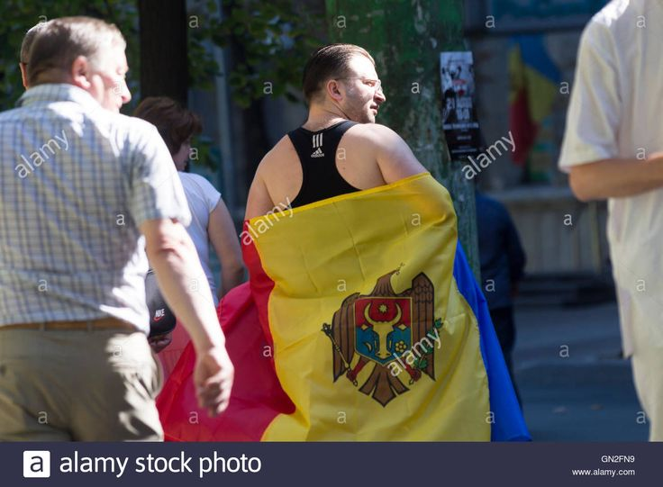Chisinau, Moldova. 27th August 2016. Man covered in Moldavian flag walking on…
