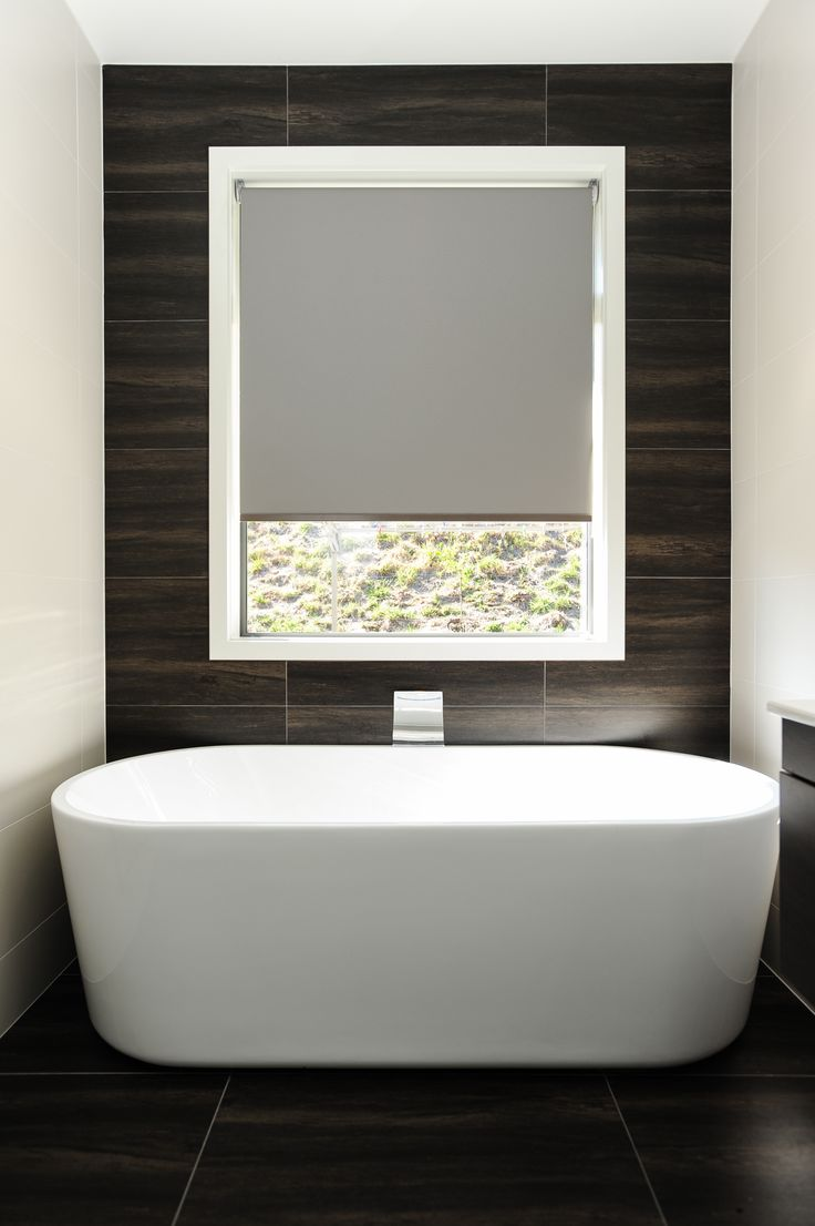 Stunning bath feature with dark wood look tiles extending from the floor up the wall and framing the view out the window.