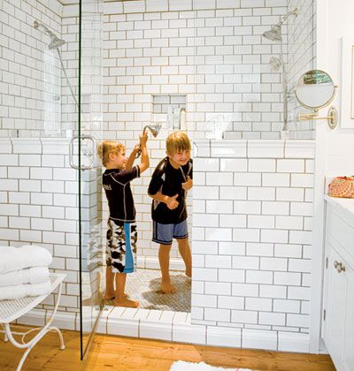 a double walk in shower in all white subway tiles, sink, and cabinetry foster an open and airy feeling...
