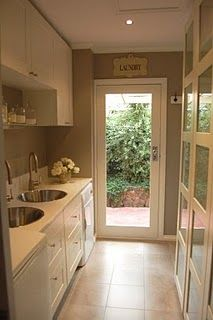 this was my inspiration for a laundry room, before we changed the location/layout...love the IKEA glass-front cabinets!  They house multiple laundry baskets inside.