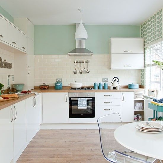 traditional green kitchen with white accents and a tasteful pastel green wall wooden flooring helps finish it nicely