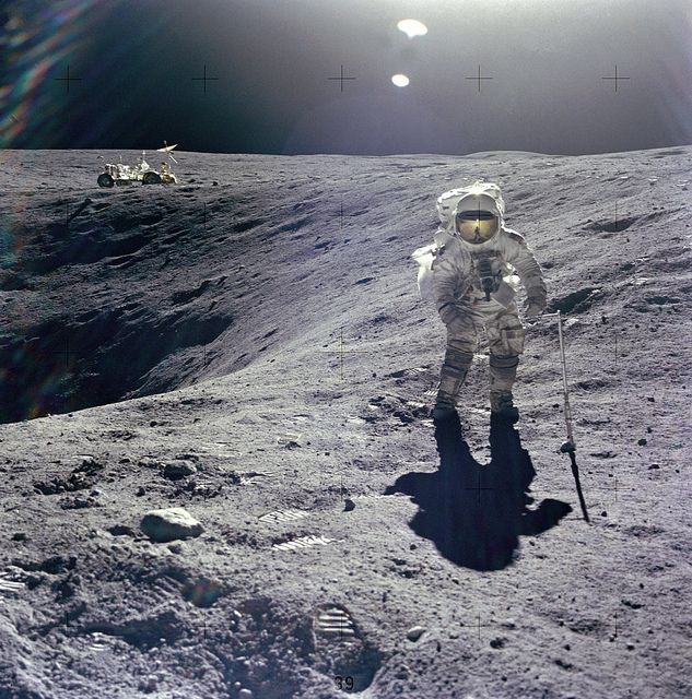 Charles M. Duke, Lunar Module pilot of the Apollo 16 mission, collecting samples. Duke is standing at the rim of Plum crater with the Lunar Roving Vehicle in the background