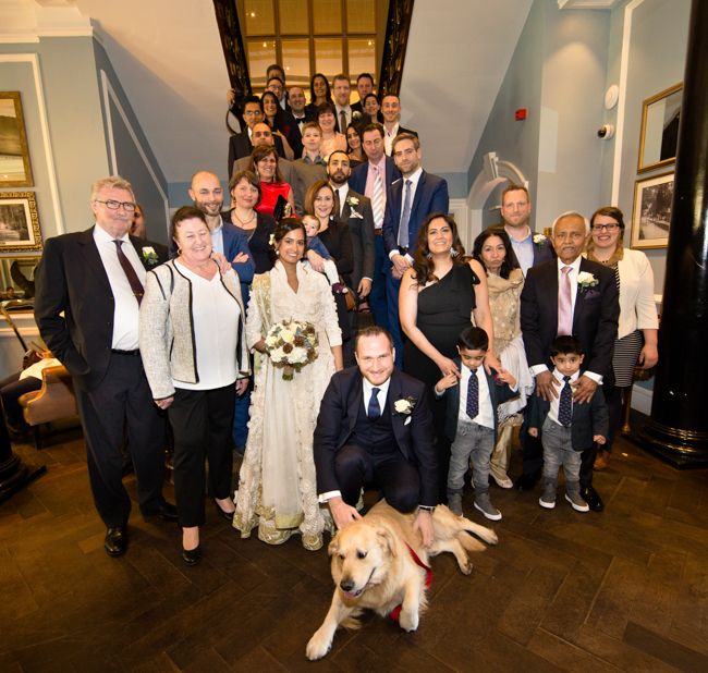 The group shot on the stairs from a wedding at Cannizaro Park Hotel, Wimbledon South London.With bride and groom and their dog.
