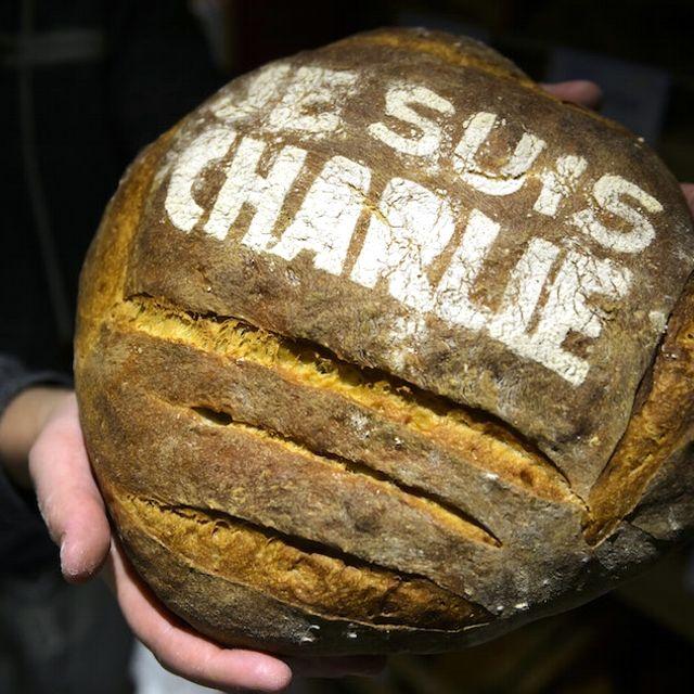 Un fornaio mostra un pezzo di pane con su scritto #JeSuisCharlie a Daillens, Svizzera
