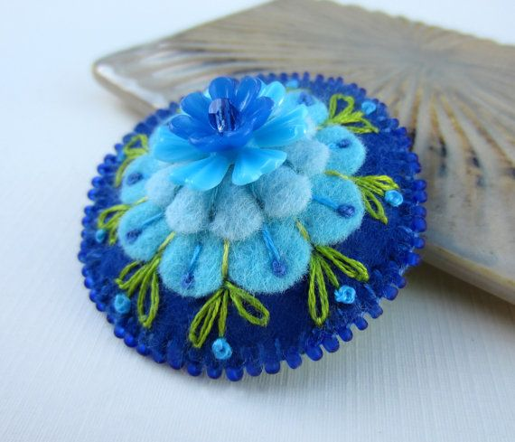 "This is ""Felt Flower Brooch"" by skippingstones, made from felt, wool, seed beads, and embroidery thread. This pretty pin features a harmony of blue flowers and green leaves. This pattern, like the red earrings, is radially repetitive."