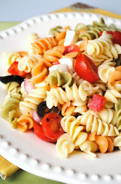 Ingredients:  1 box Tri-Color Rotini   1 can sliced black olives, drained  1/4 red onion, diced  1/2 cup diced Mozzarella chunks  1/2 cup sliced grape tomatoes  1/2 red bell pepper, diced  1/2 cup of peeled and quartered cucumber  1/2 cup Italian dressing   Salt and pepper to taste