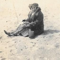 Woman on a beach in hat and coat
