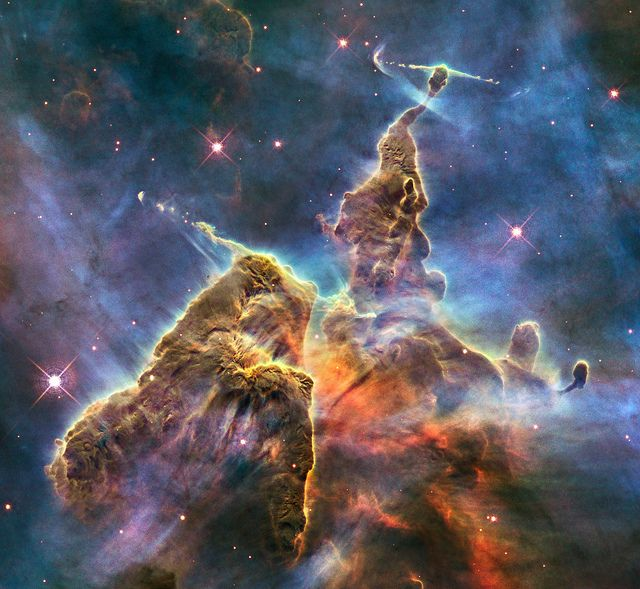 "Hubble photo: ""small portion of one of the largest seen star-birth regions in the galaxy, the Carina Nebula. Towers of cool hydrogen laced with dust rise from the wall of the nebula... The image captures the top of a three-light-year-tall pillar of gas and dust that is being eaten away by the brilliant light from nearby bright stars. The pillar is also being pushed apart from within, as infant stars buried inside it fire off jets of gas that can be seen streaming from towering peaks..."""