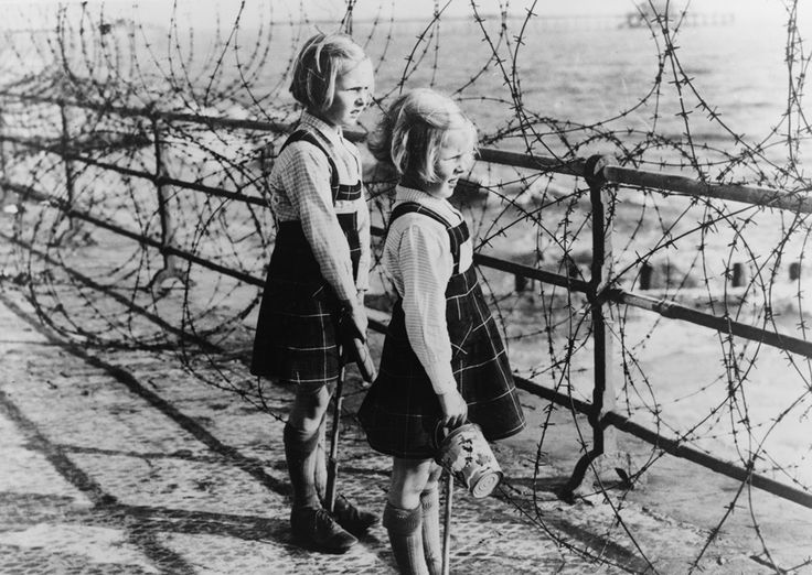 Two girls on the south coast of England look out toward the beach through a barbed wire fence constructed as part of Britain's coastal defenses (LOC): World War, The South, Britain Coastal, Barbed Wire, British Girls, War Ii, South Coast, Wire Fence, Fence Construction