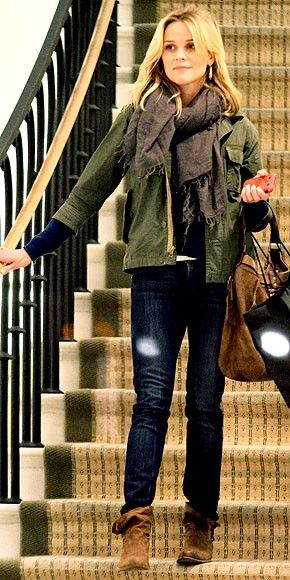 Reese Witherspoon in skinny jeans, navy top, olive jacket, grey fringe scarf and brown boots or booties.