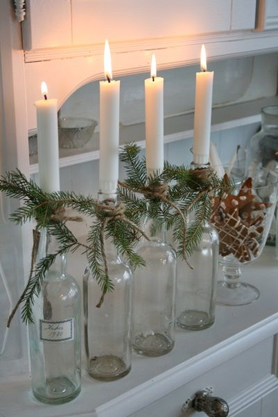 Simple candles in vintage bottles with pine and twine