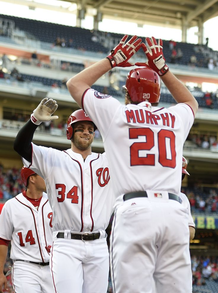 Harper hits 1st slam, 100th HR; Nationals drop Braves to 0-9 | Washington Nationals' Bryce Harper (34) celebrates his grand slam with Daniel Murphy during the third inning of an baseball game against the Atlanta Braves, Thursday, April 14, 2016, in Washington. This was Harper's 100th home run of his career. Also seen is Washington Nationals center fielder Chris Heisey (14).