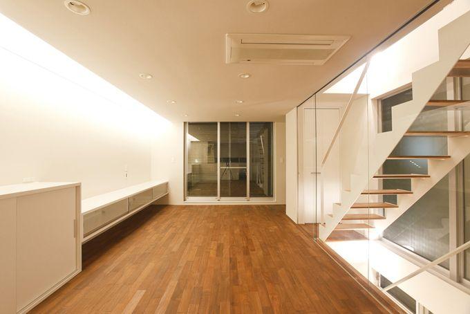 北側の大きな壁に間接照明のあるリビング ガラス張りの階段室