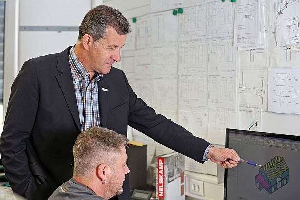 Siegfried Weiss (stehend), Inhaber und Geschäftsführer der Bittermann & Weiss Holzhaus GmbH in Großrinderfeld, ist 2008 in den Main-Tauber-Kreis gezogen. Foto: djd/Karin Ludwig/Wirtschaftsförderung Main-Tauber-Kreis