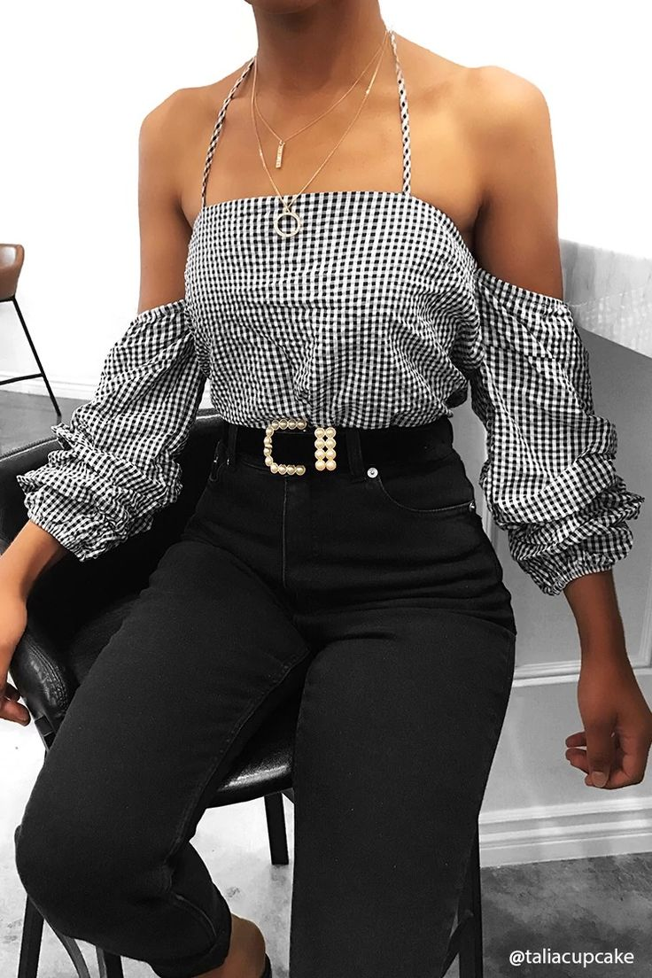 A woven top featuring a self-tie halter neckline, an allover gingham print, 3/4 sleeves with open shoulders and darted detail, an elasticized back and sleeves, a concealed back zipper, and flowy fit.