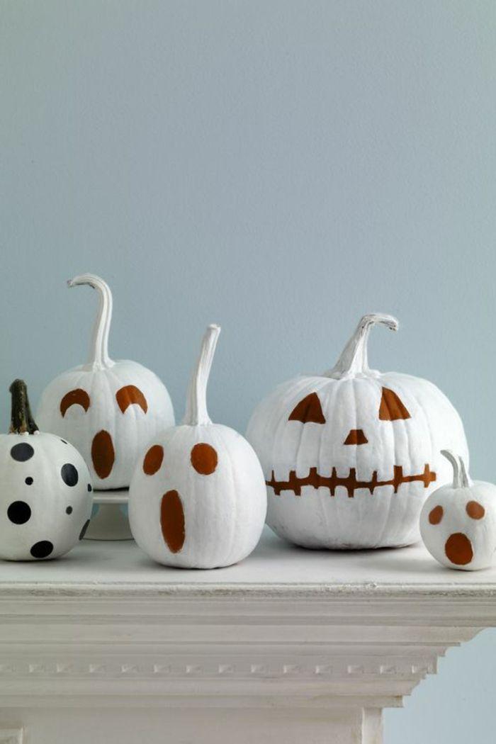 fotos de calabazas de Halloween, calabazas blancas con caras pintadas sobre mesa