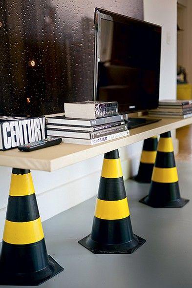 Certos cones de rua têm a ponta achatada, o que os torna pés perfeitos para improvisar um rack. Sobre quatro cones, apoiou-se uma porta. Para manter o equilíbrio, distribua as peças por toda a madeira. Produção de Ana Wenzel