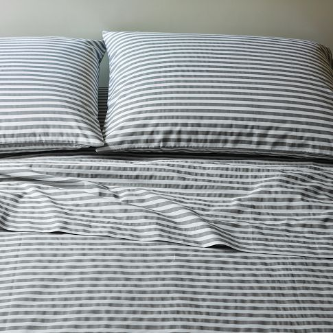 gray and white striped sheets (with a dark gray duvet on top and a white or mustard yellow throw at the foot of the bed)