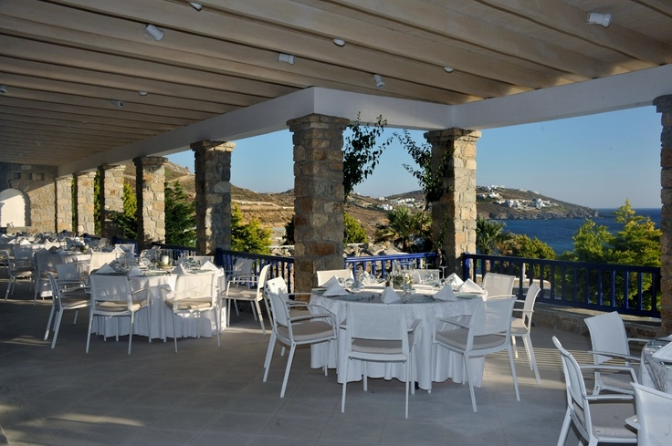 The terrace of Dolphins of Delos Restaurant set with round tables - Mykonos Grand Hotel & Resort