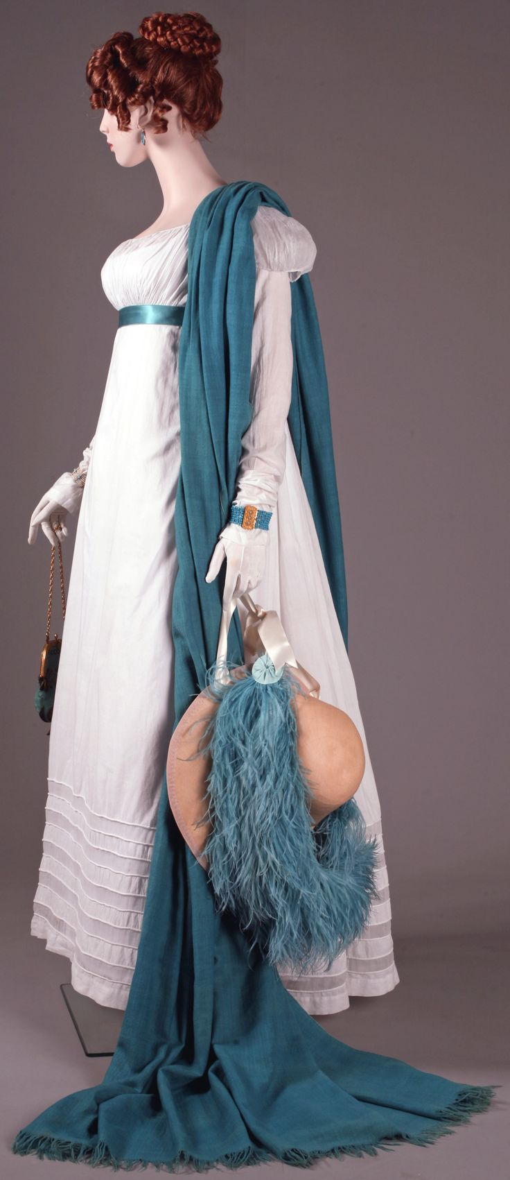 "Annette, from ""Napoleon and the Empire of Fashion"" exhibition. Dress. Cotton percale, cotton muslin, cording, France or England 1814-15. Shawl, cashmere, England, first quarter of the XIX century. Jewellery. Gold, turquoise and micro mosaic. Italy and England, first quarter of the XIX century. Bag. Vermeil, silk and gold tricot, gold bullion. France, circa 1808."
