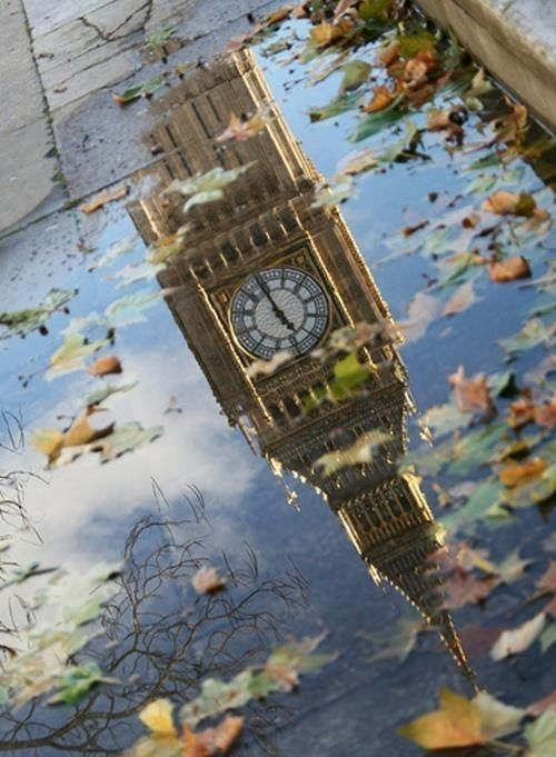 Big Ben reflected in a leaf filled puddle on the sidewalk… London