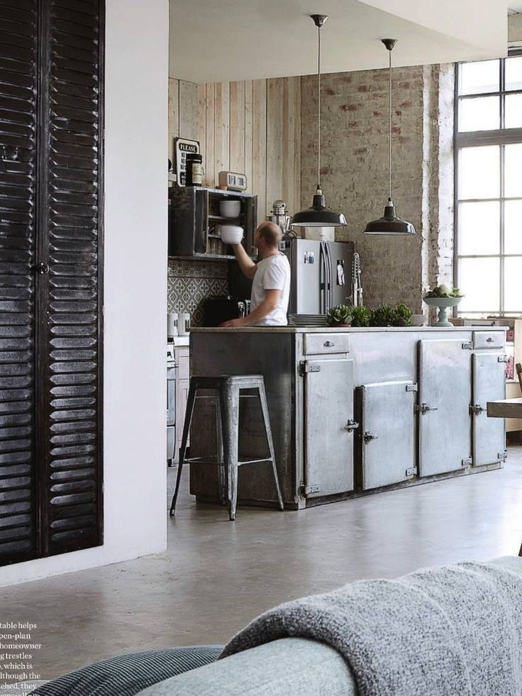 Industrial kitchen - love the mix of brick and wood with iron and steel in the background, and then you have the softer side in the foreground with blanket and couch and old shutters.