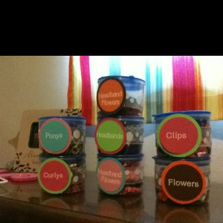 Storage idea for my daughter's hair accessories; containers from the dollar store and ribbon, paper and letters from a craft store. Easy and cheap solution for the messy accessory drawer in her bedroom!