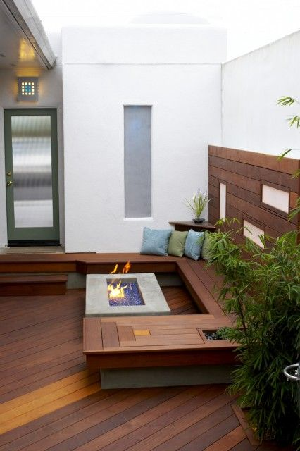 A private, walled breezeway features a bamboo wood deck and a fire pit surrounded by built-in bench seating.  (via Jeffrey Gordon Smith Landscape Architecture)