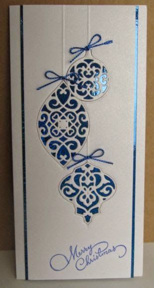handmade Christmas card from serendipity ... tall and narrow format ... shiny blue metallic layer behind white ... luv the trio of die cut filigree ornaments placed back into the spot they were cut from ... elegant and pretty ...