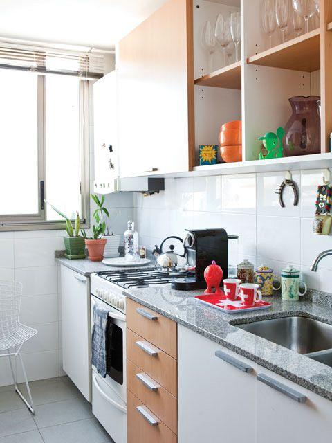 Luminosa cocina de un departamento con alacenas en marrón y blanco, bandeja con tazas de Suiza, cafetera y piso de cerámica color gris.