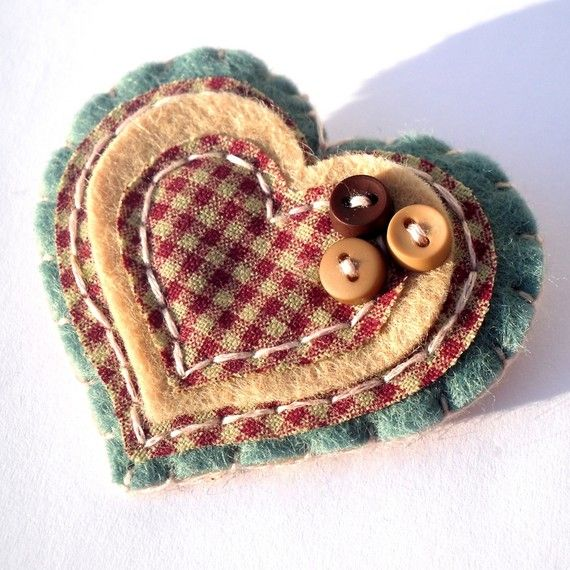 A beautiful hand sewn brooch with layers of soft green and cream felt and red gingham fabric. The brooch is heart shaped and each layer has been