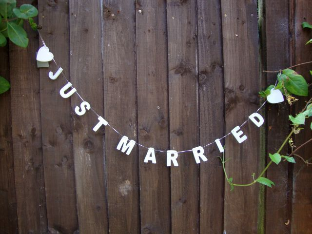 'Just Married' Wooden Garland - maybe out of  fabric or paper to hang over or in front of your table at the reception?