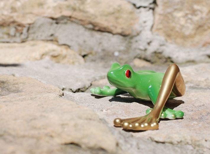 Figurka Żaba z długą złotą nogą w nowej zielonej dekoracji.