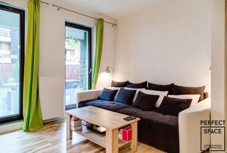 Wnętrze salonu z przytulną sofą z mnóstwem ilości poduszek. Zielone zasłony wprowadzają energię do salonu.