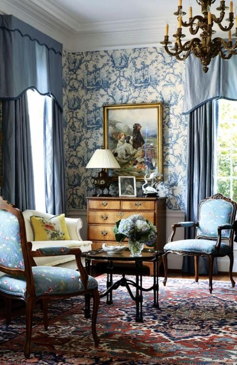 A lovely formal living room. The rug adds pattern so the solid draperies & simple upholstery work well. The wood pieces show up well against the blue. Elegant & tasteful.