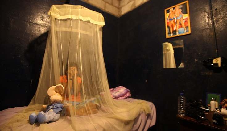 """Violeta, a prostitute at """"La Noche"""" Brothel on San Cristobal Island in the Galapagos, covers her face to protect her true identity while sitting beneath a mosquito net in her bedroom. Prostitution is legal in Ecuador, and the girls that enter into the business are given a license to work as a prostitute within the country. Kathryn Carlson/reesenews"""