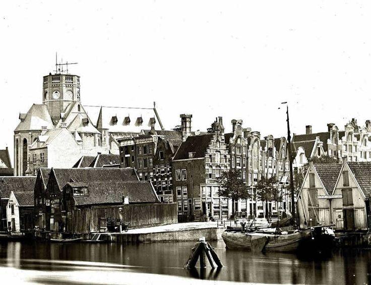 Amsterdam, de bouw van de Posthoorn (1860-1863). Op de voorgrond het Westerdok met daarachter de hoek Korte Prinsengracht-Haarlemmer Houttuinen. Op de wallekant de loodsjes die in de plaats kwamen van de houttuinen en op hun beurt eind 19de eeuw weer moesten plaatsmaken voor nieuwe woningen.