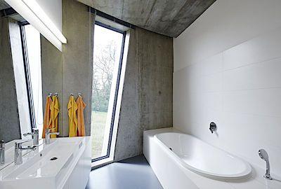 Interiér koupelny je nesen v lehkém kontrastu šedé a bílé barvy. Pohled z vany skrze prosklení do volné přírody povyšuje koupelnu na relaxační místnost par excellence.