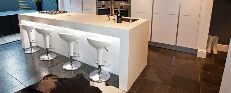 Contemporary kitchen island design with seating in a Polar white kitchen finish and White Corian worktop and breakfast bar. #whitekitchen #kitchenisland