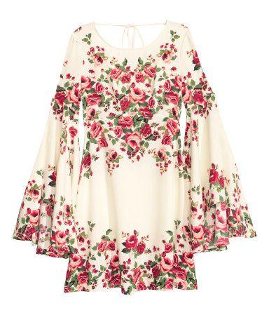 Naturhvid/Rødblomstret. Kort kjole i tynd, vævet kvalitet med trykt mønster. Kjolen har trompetærmer og er skåret i taljen. Dybere udskæring bagpå med