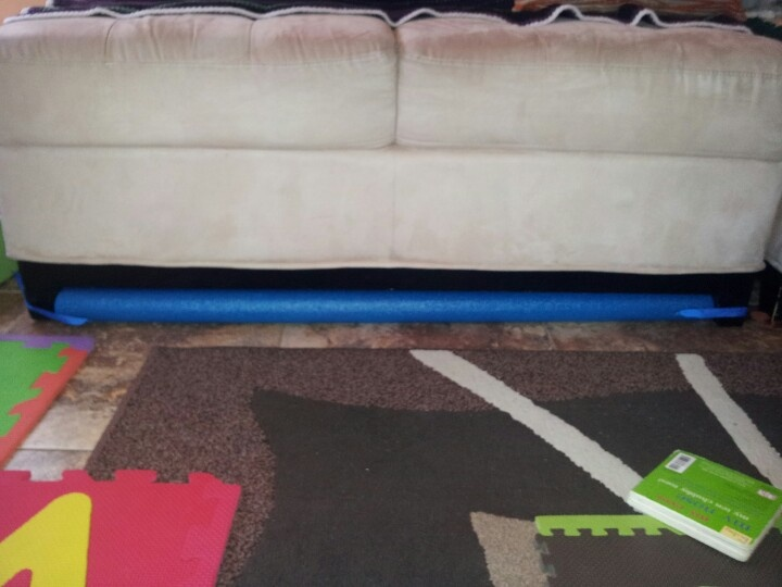 Hate it when the toys disappear under the couches? I used to until I invented the TOY STOPPER! Make your own toy stopper, it's Super Easy and so Worth it. Use a pool noodle, you may need more than one depending on the length of your couch, cut to the length if needed. If you need more than one tape it together with electrical tape. String a ribbon at each end and tie around the foot of your couch. And presto... You have a toy stopper. Hope this helps with your play area. ;)