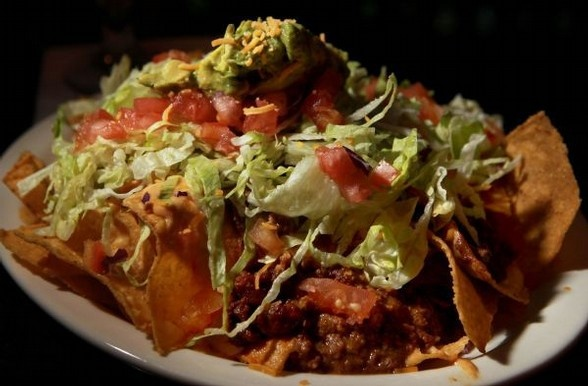 Mr. Bruce's Nachos at Molly's La Casita is a classic example of the bar-munchies staple: cheese sauce and chili, crisp lettuce, peppers and tomatoes, topped off with sour cream and guacamole. (Nikki Boertman/The Commercial Appeal): Cheese Sauce, Favorite Restaurant, Restaurant Dishes