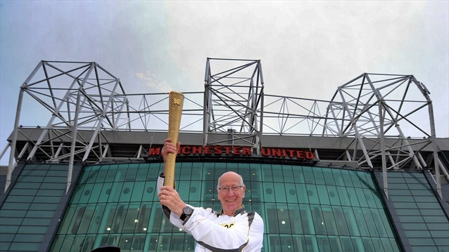 Sir Bobby Charlton holds the Olympic Flame outside Old Trafford football stadium on Day 37 of the London 2012 Olympic Torch Relay.