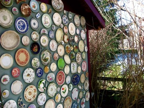 Garden upcycling ideas: Create an outdoor plate wall display on your garden shed