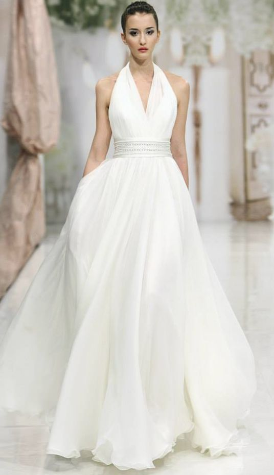 Sophisticated white halter wedding dress with cinched waist detail; Featured Dress: Atelier Emé